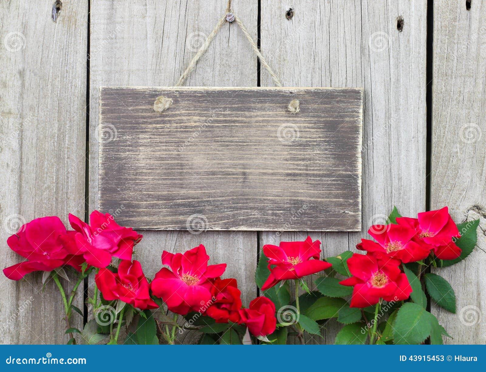 Blommor som gränsar det tomma lantliga trätecknet som hänger på ...