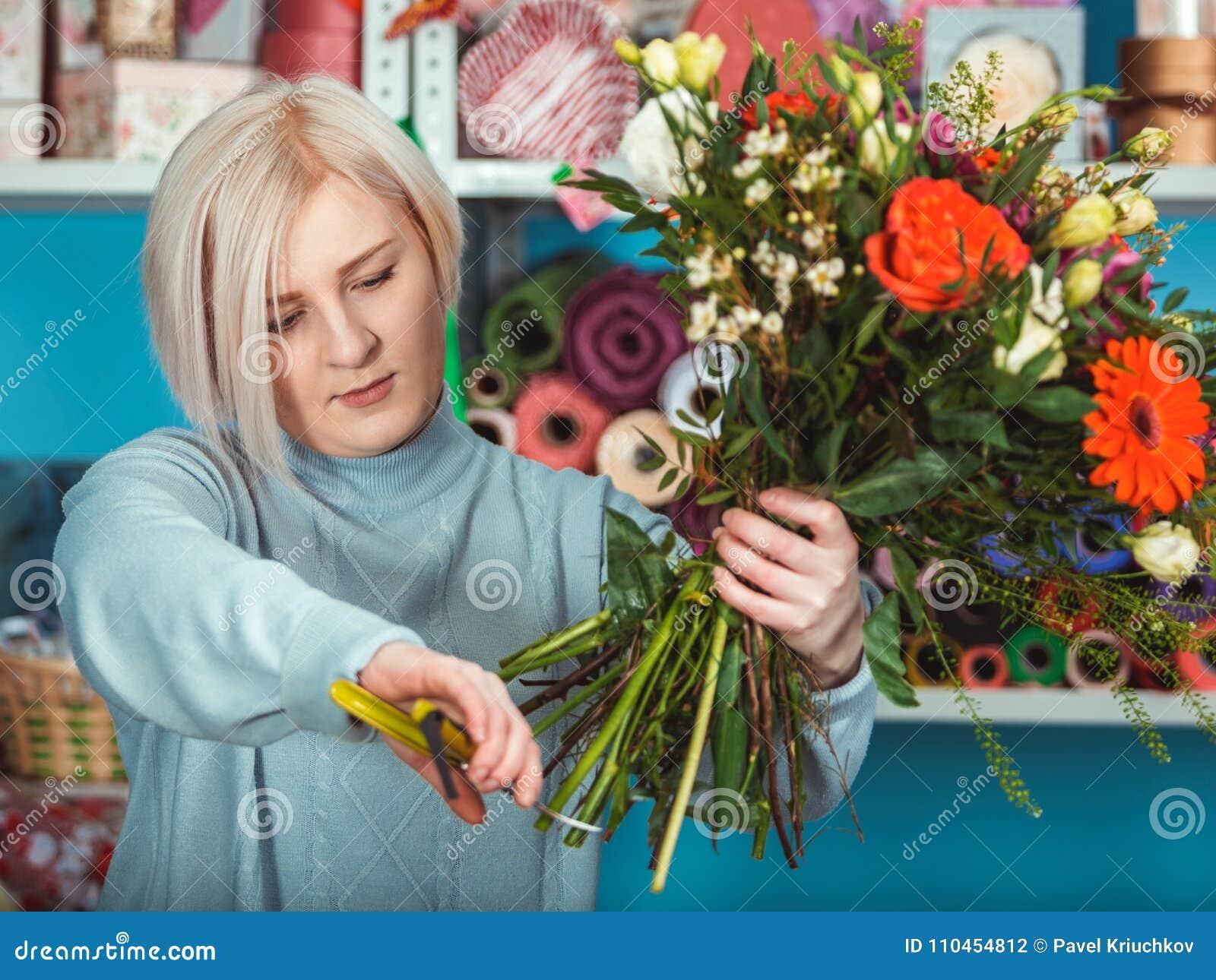 Blomsterhandlare i arbetsplatsen blommaillustrationen shoppar smellcomp Stående av en le kvinna