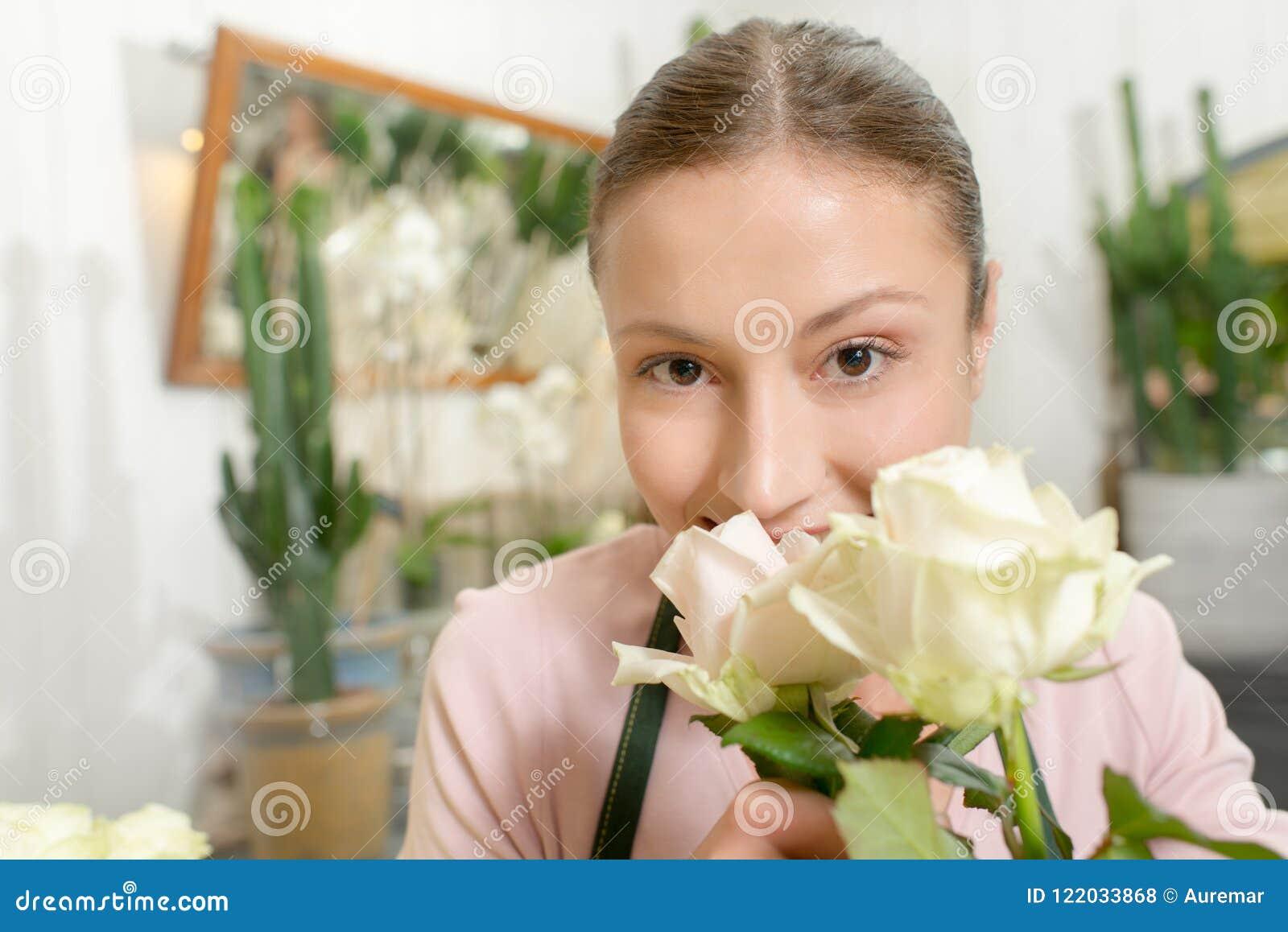 Blomsterhandlare som luktar vita rosor