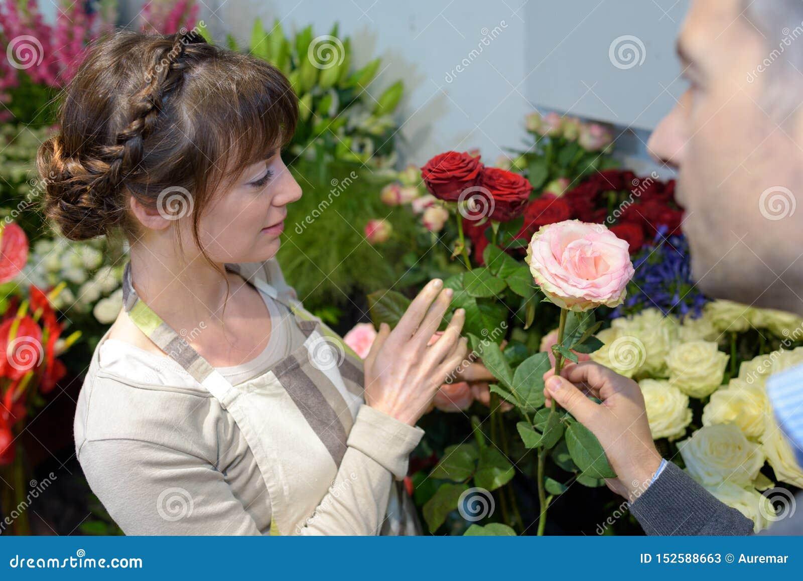Blomsterhandlare som talar till kunden och ger rådgivning