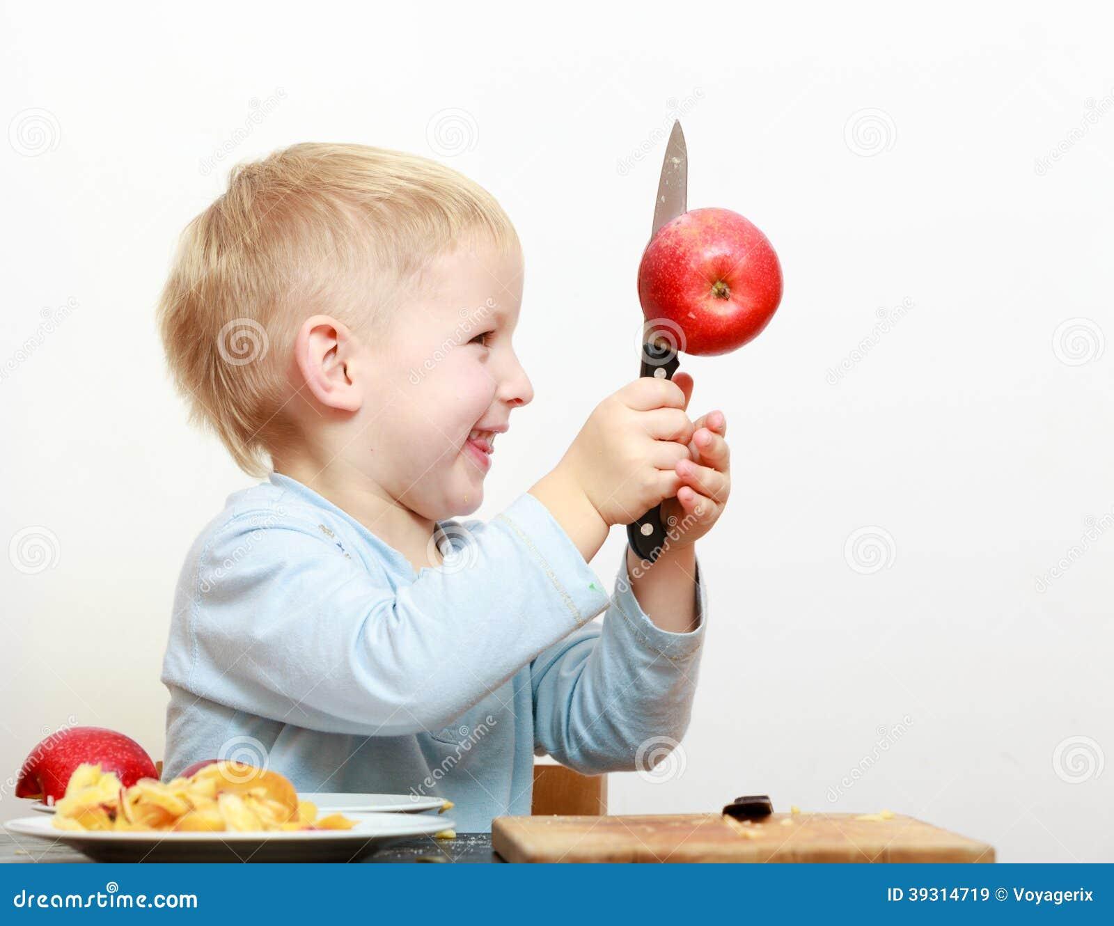 Blond boy child kid preschooler with kitchen knife cutting fruit apple