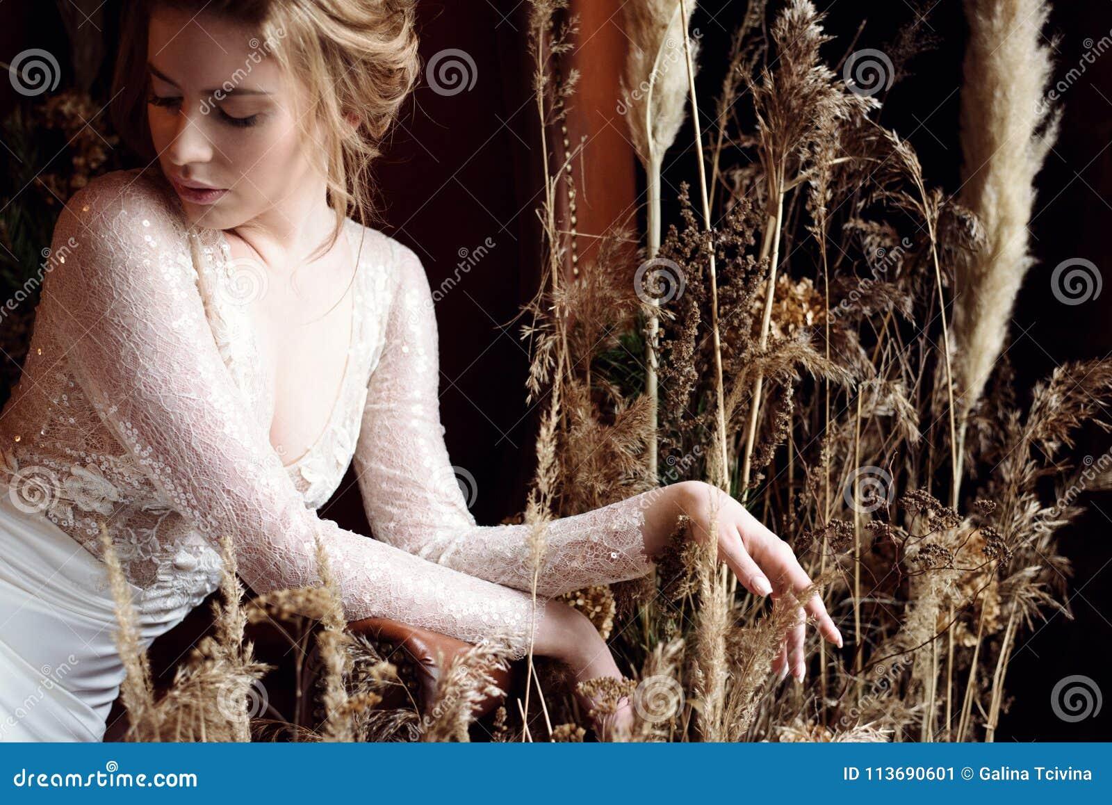Blond brud i den vita bröllopsklänningen för mode med makeup