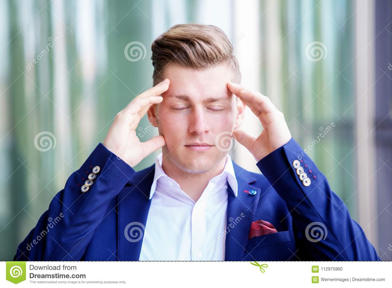 Blond businessman standing outside with his eyes closed