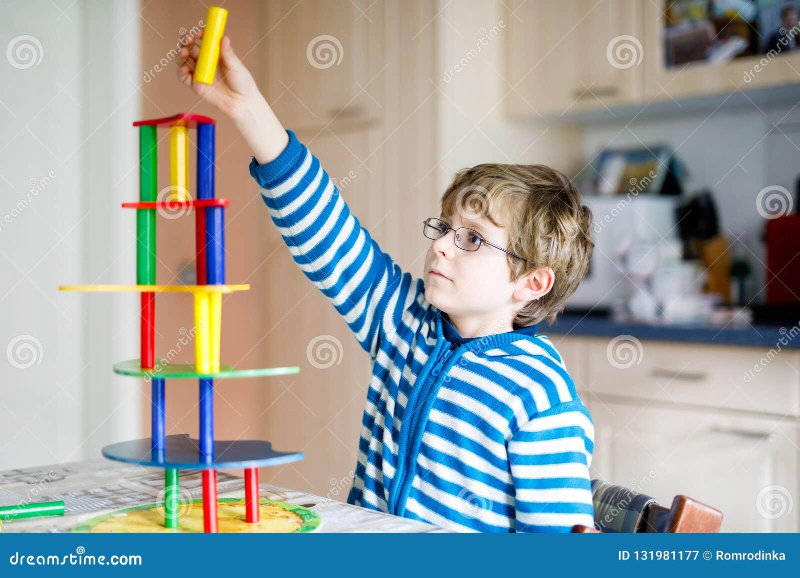 Blond dziecko z szkłami bawić się z udziałami kolorowa drewniana blok gra salowa Aktywna śmieszna dzieciak chłopiec ma zabawę z