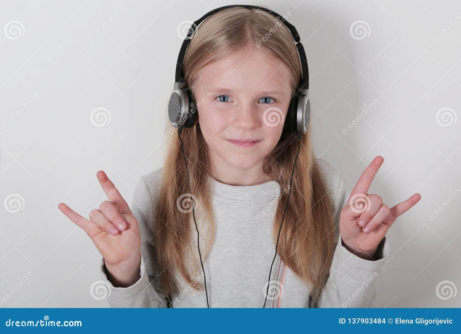 Blond dziewczyna słucha muzykę i śpiew z hełmofonami Śliczna mała dziewczynka robi rolce podpisywać