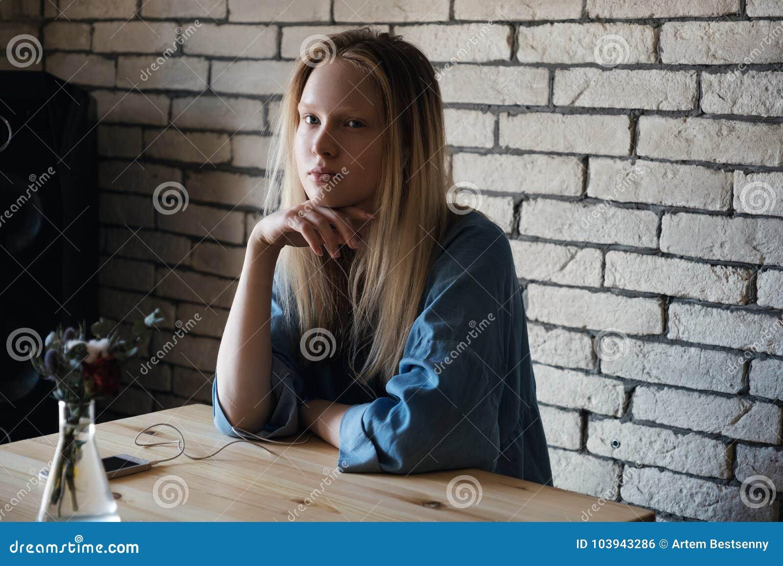 Blond dziewczyna siedzi z hełmofonami i patrzeje zamyślenie daleko od, z jej ręką na jej podbródku