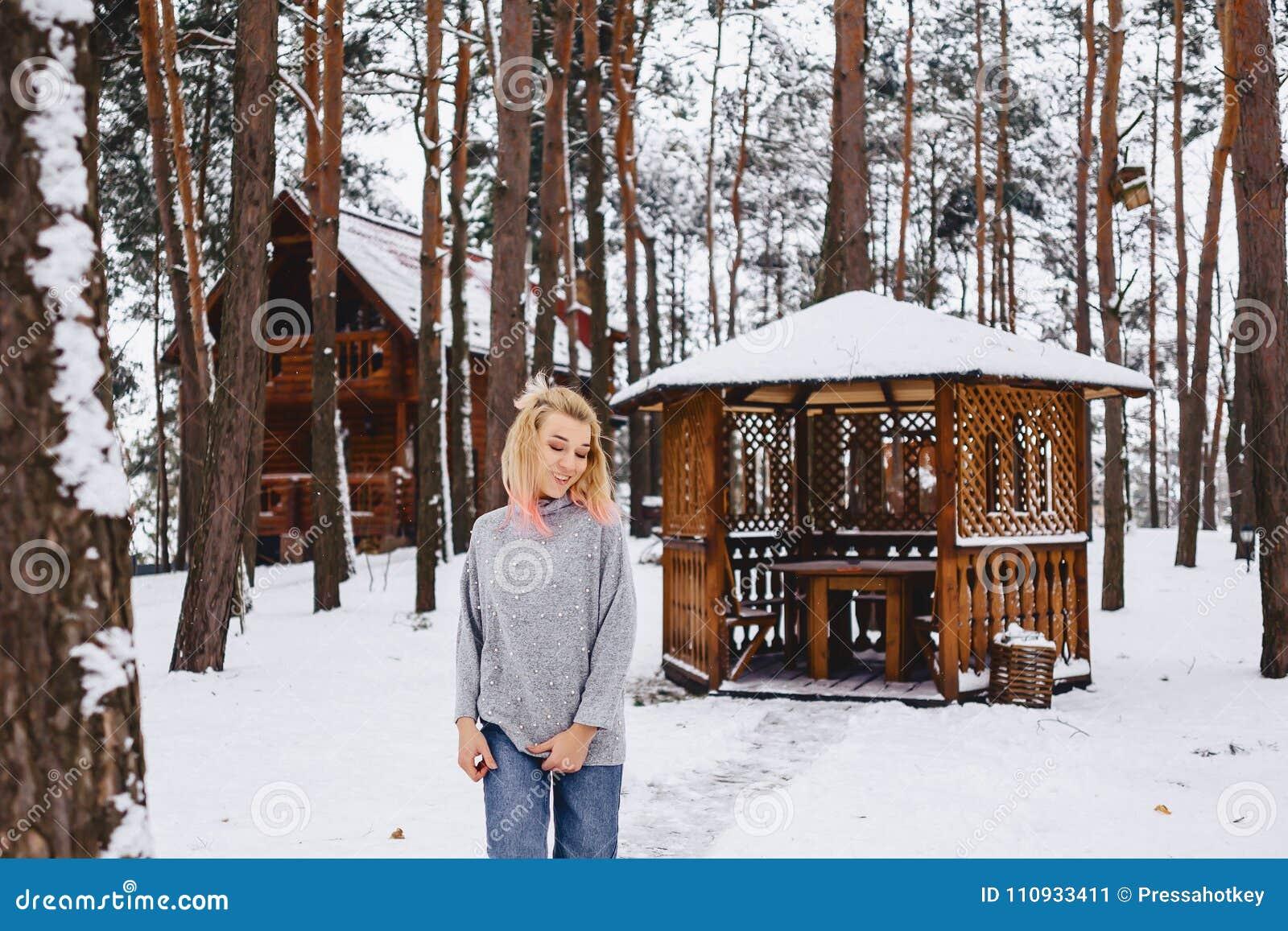 Blond dziewczyna spacer blisko gazebo w zima lesie