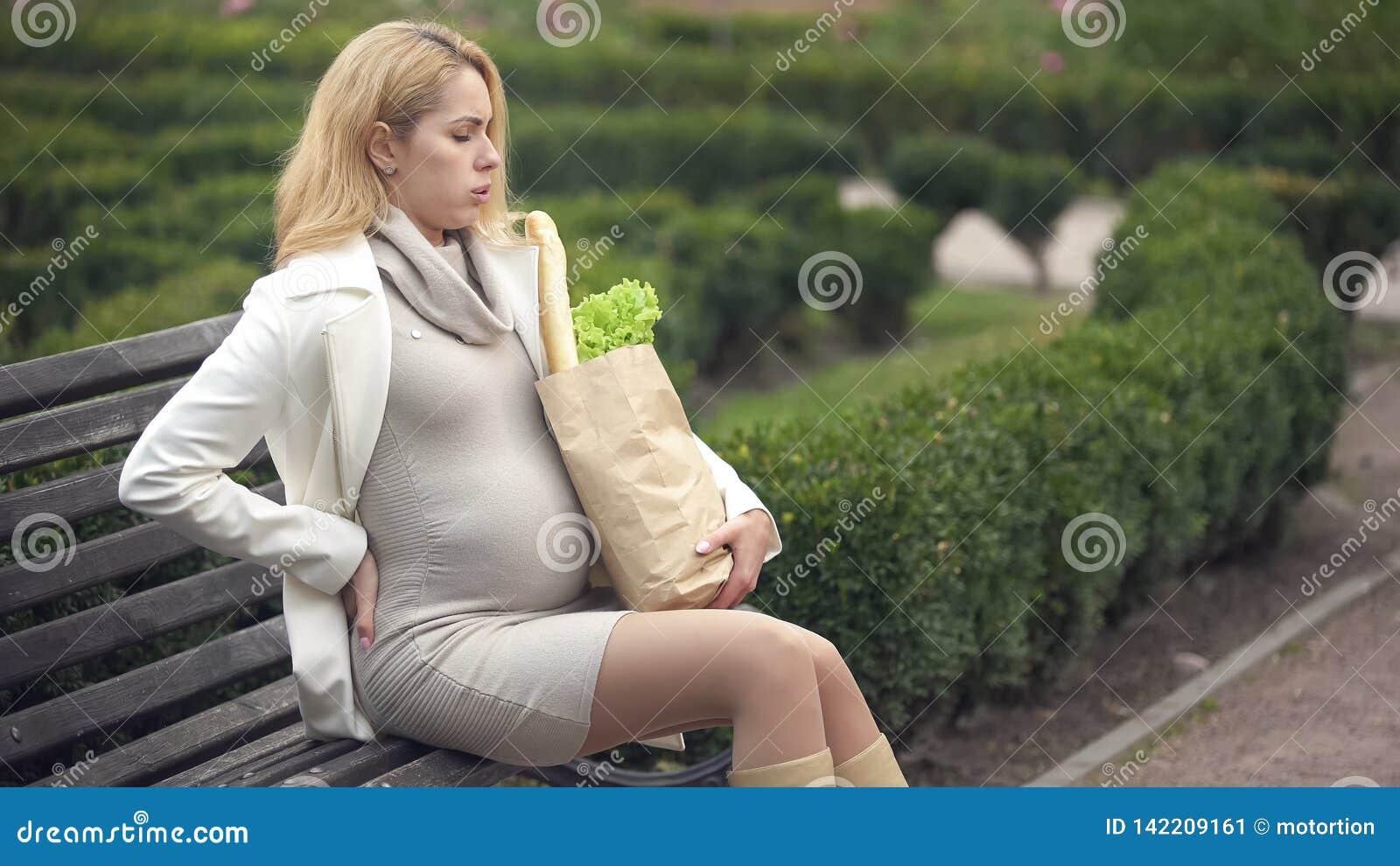 Blond förväntande dam som vilar påsen för bänkinnehavlivsmedelsbutik, havandeskapsvårigheter