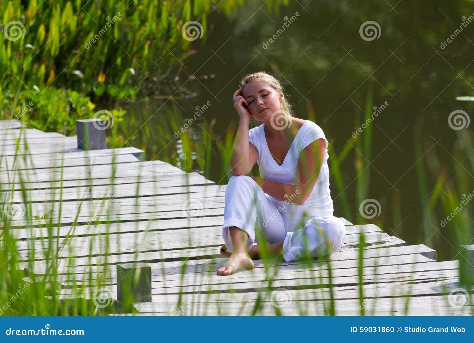 Blond flicka för 20-tal som kopplar av och dagdrömmer nära vatten