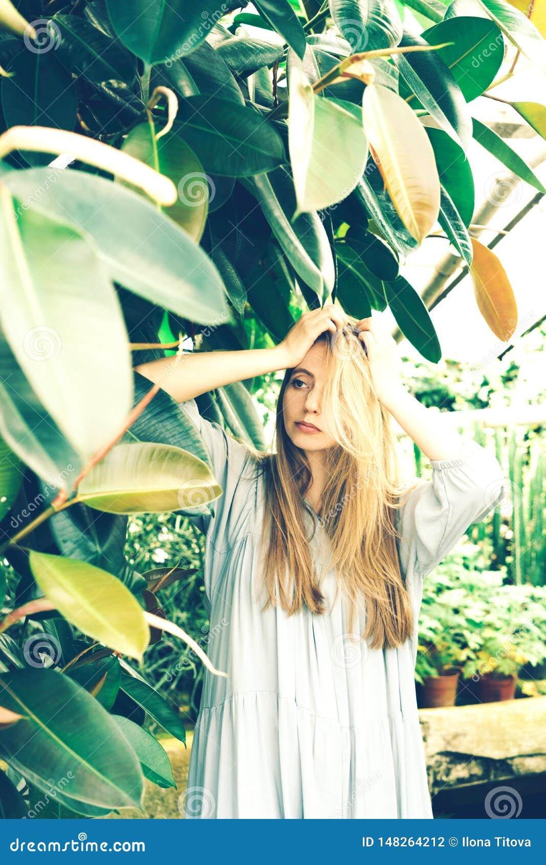 Blond flicka i en tropisk buske i växthuset