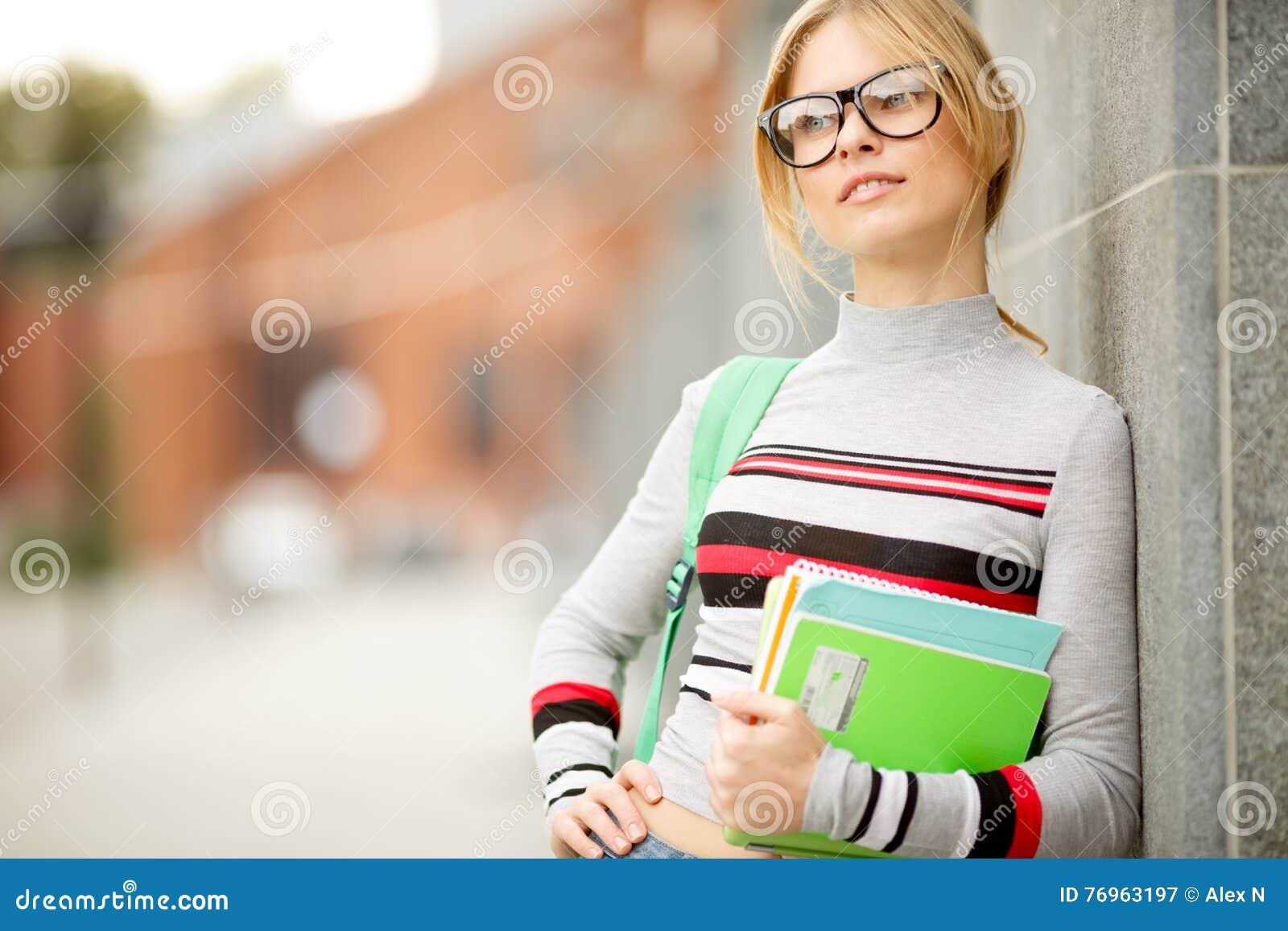 Blond flicka som lutas på väggen av byggnad