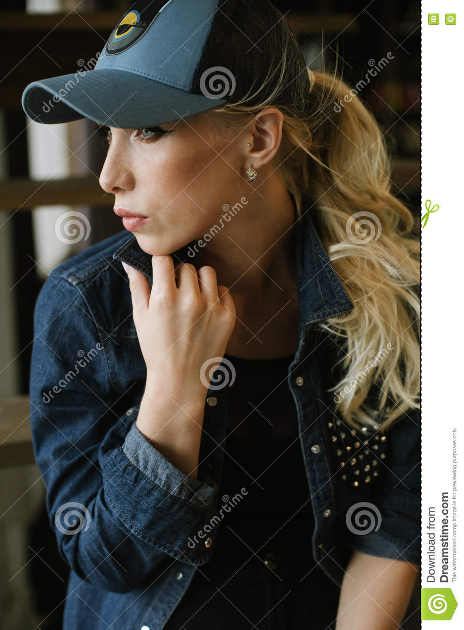 Cute long-haired girl in jeans jacket and a baseball cap sitting on the  wooden stairs posing 969b9f39264