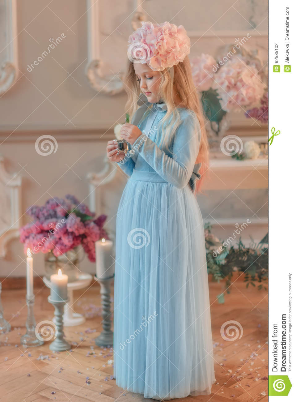 Blond Girl In Blue Dress And With A Flower On The Head Stock Photo