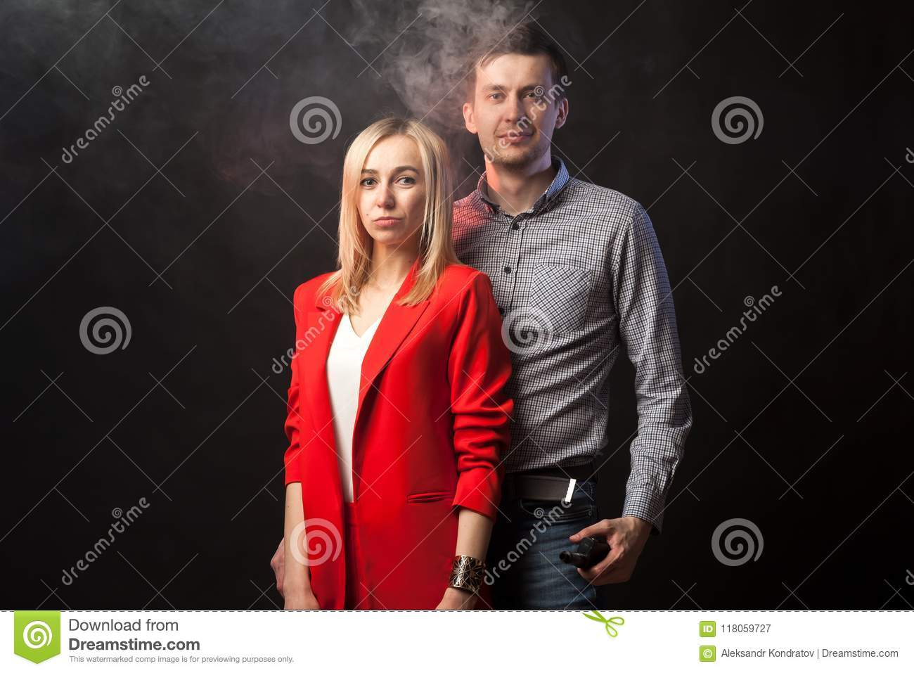 Blond girl in brightly red suit with jacket and white blouse and tall dark-haired guy
