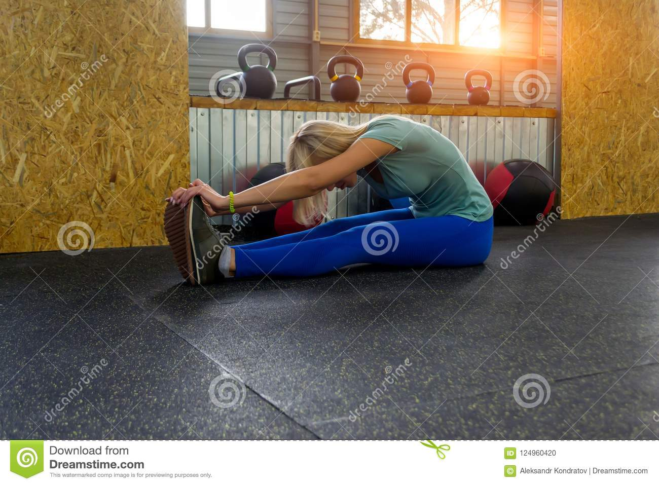Blond girl is doing stretching by sitting on the floor bending o
