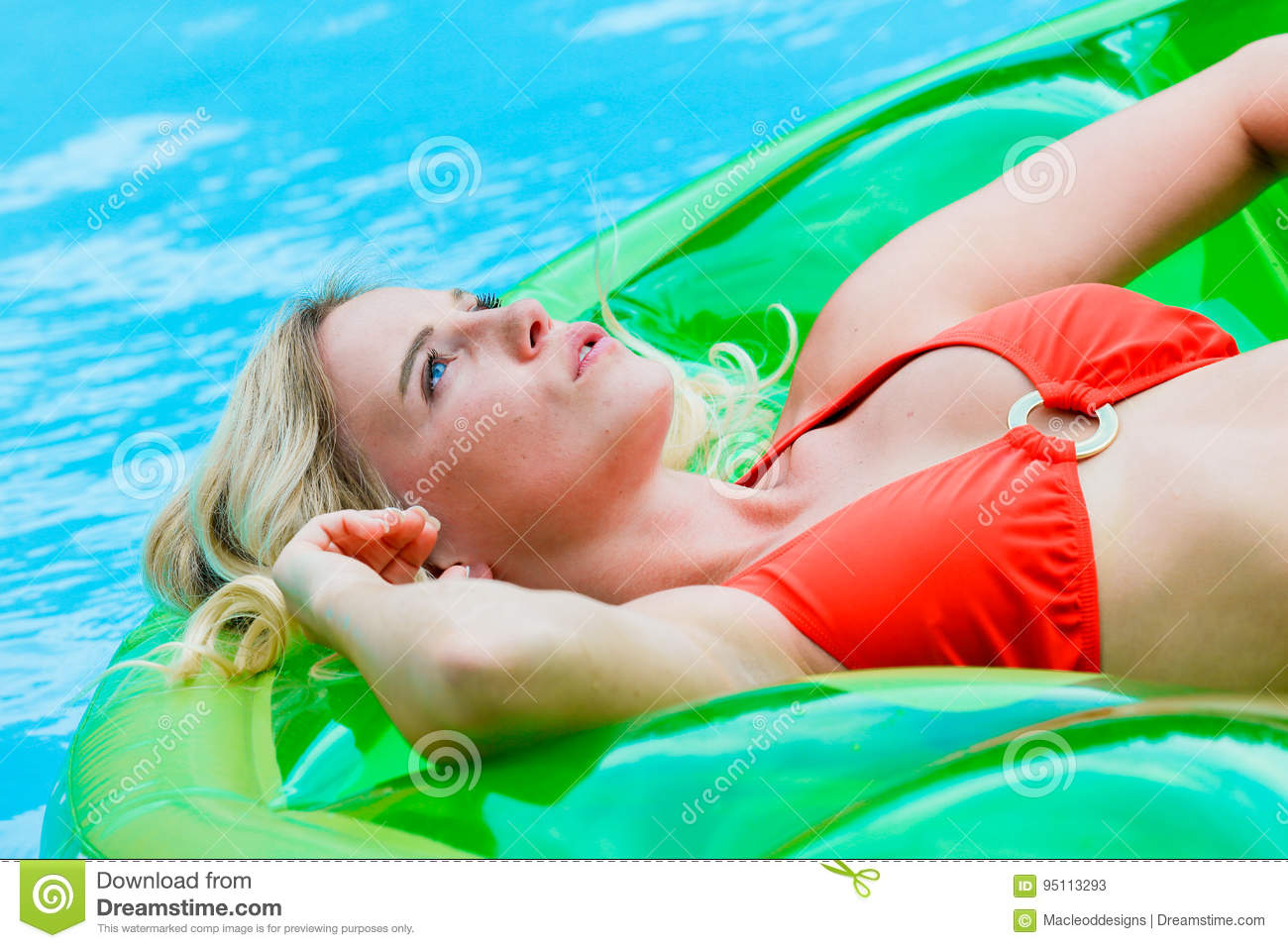 Blond girl on inflatable in pool