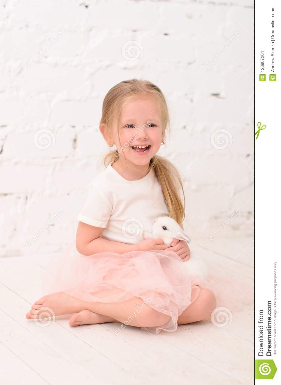 blond girl sitting with rabbit