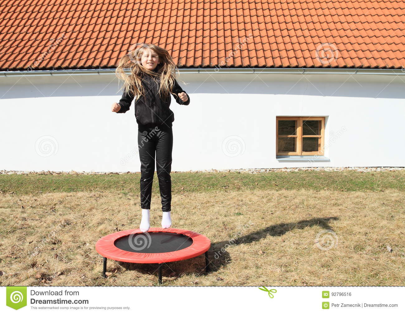 1ce39f9e Blond little girl - smiling hairy kid jumping on black and red kids´ small  trampoline standing on grass of meadow in front of white village house with  ...
