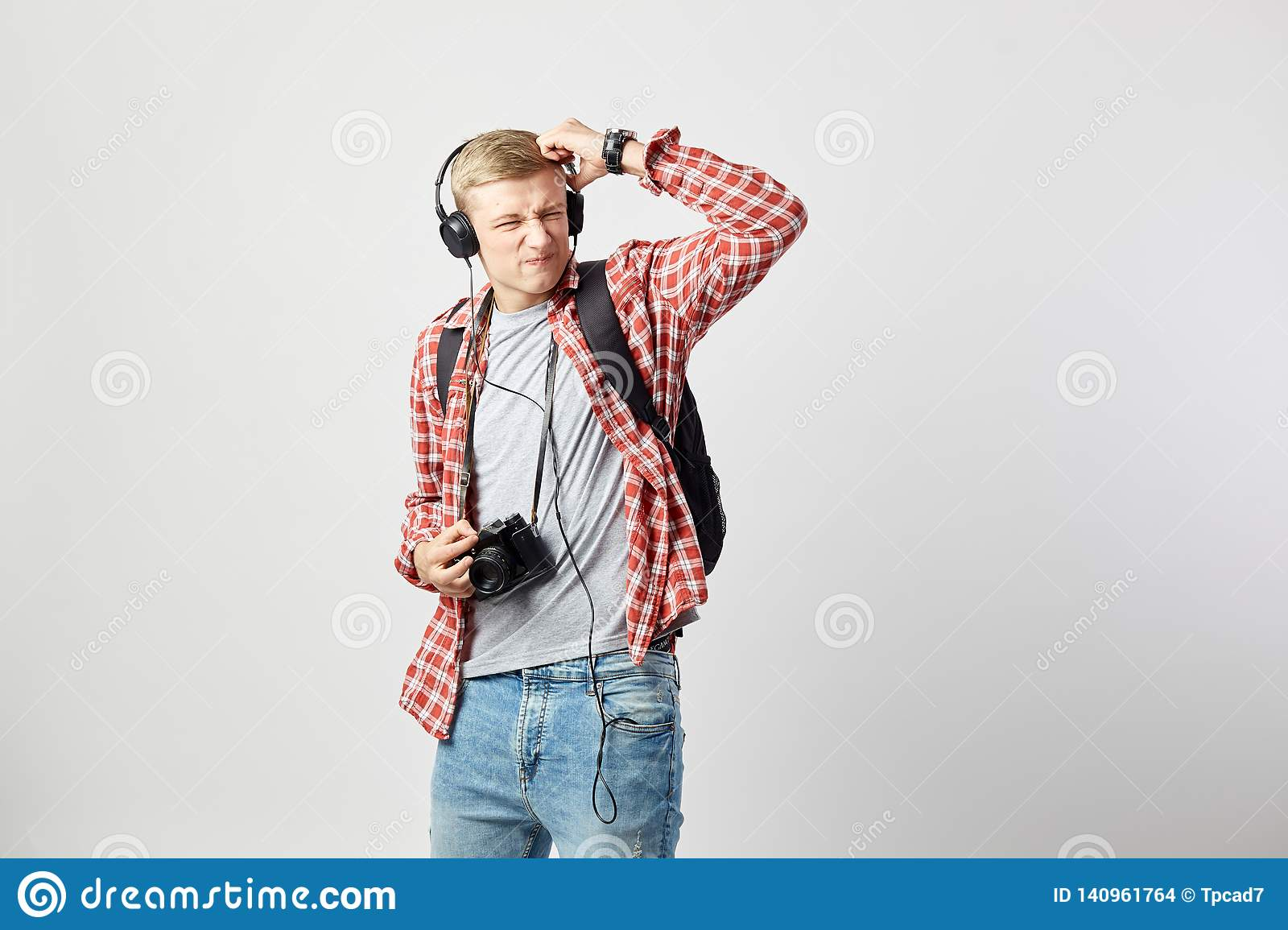 Blond guy in headphones, with black backpack on his shoulder dressed in a white t-shirt, red checkered shirt and jeans
