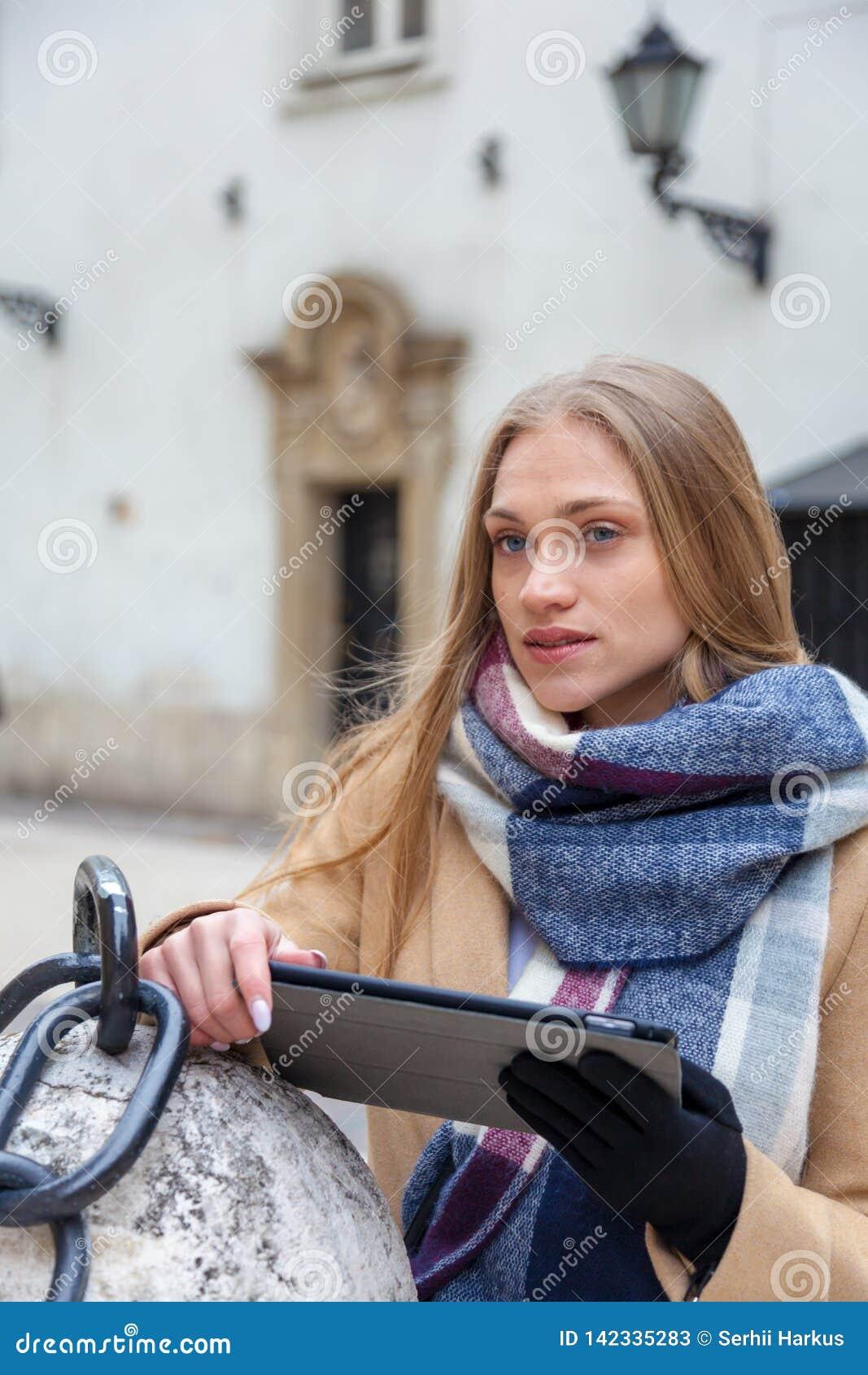 Blond härlig kvinnainnehavminnestavla på stadsgatan