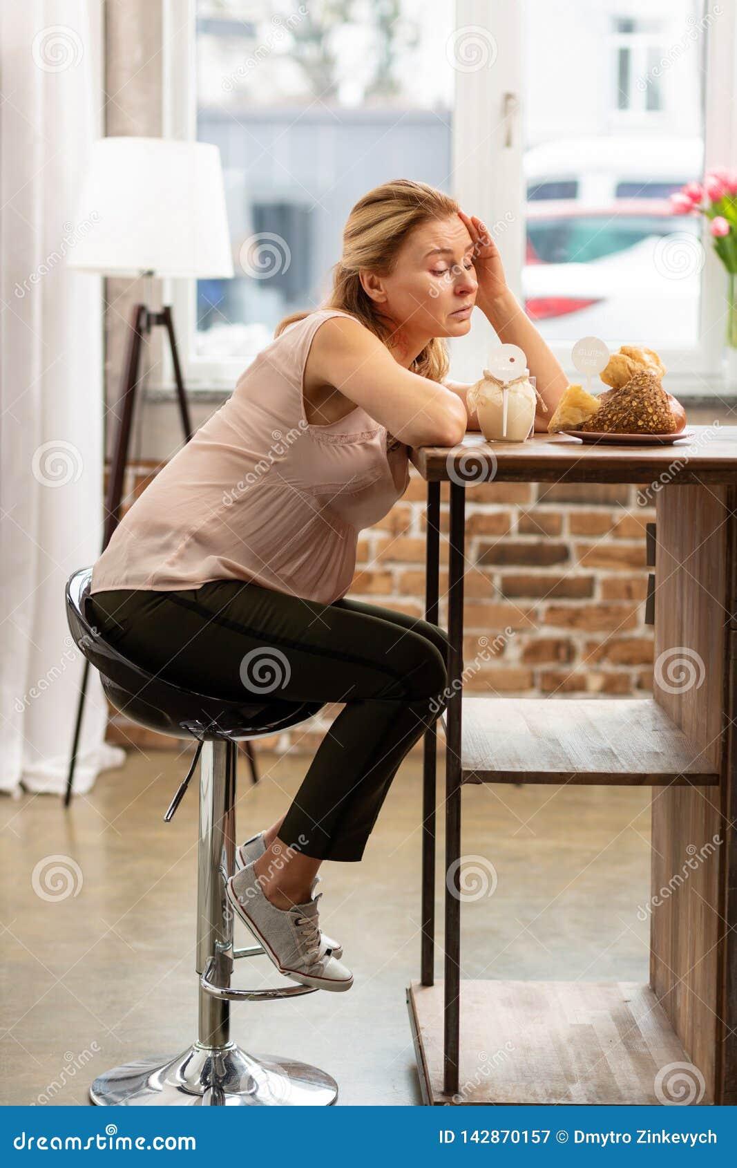 Blond-haarige Frau, Die Auf Stuhl Sitzt Und Allergische