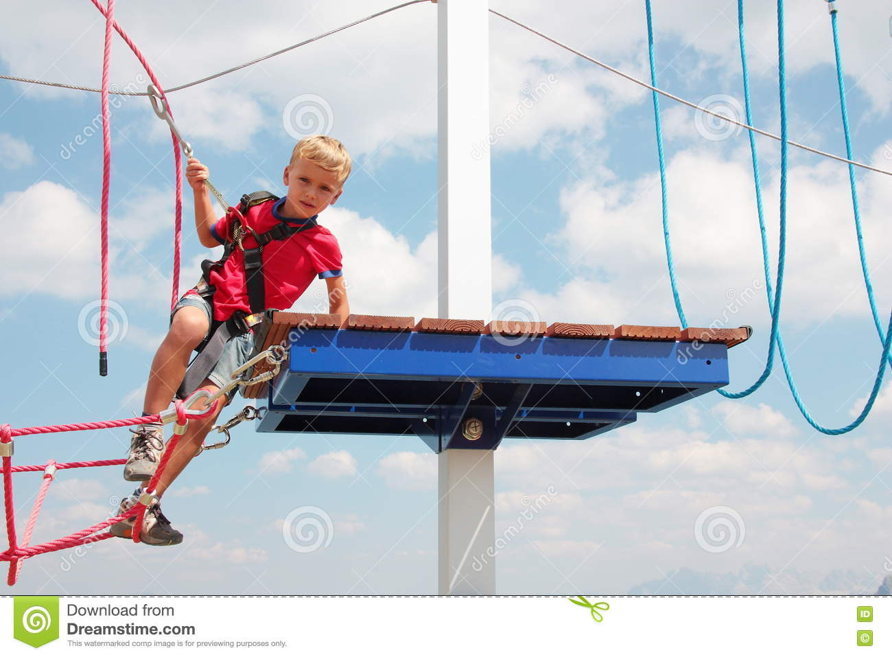 Blond hair kid playing rope course outdoor