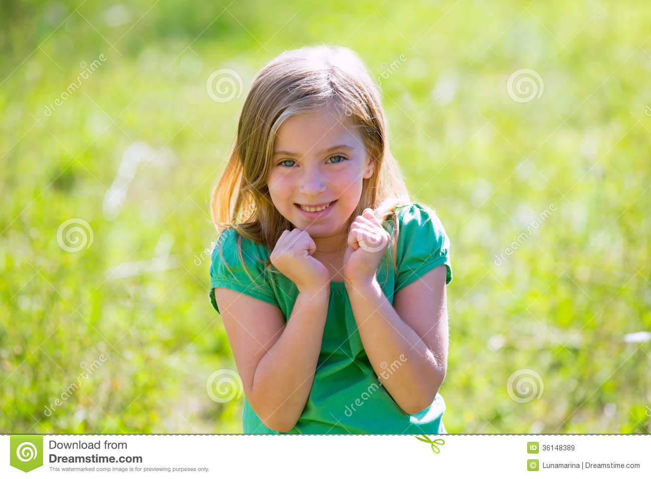 blond kid girl excited gesture expression in green outdoor stock