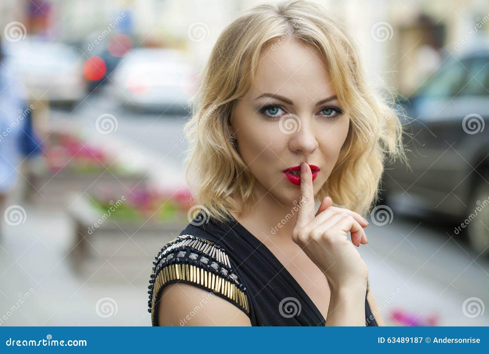 Blond kobieta stawiał forefinger wargi jak znaka cisza
