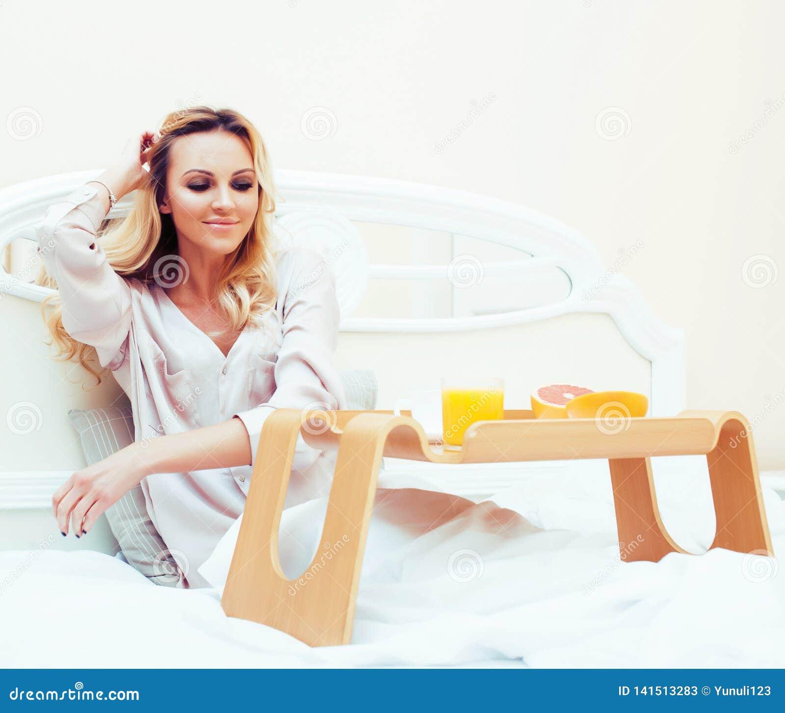 Blond kvinna för ung skönhet som har frukosten i den tidiga soliga morgonen för säng, inre rum för prinsessahus