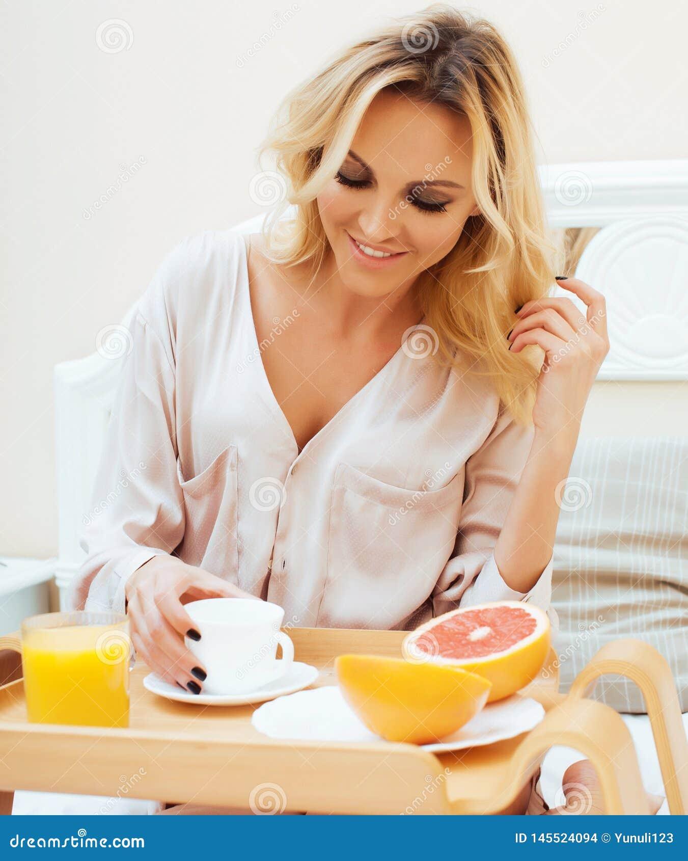 Blond kvinna f?r ung sk?nhet som har frukosten i den tidiga soliga morgonen f?r s?ng, inre rum f?r prinsessahus