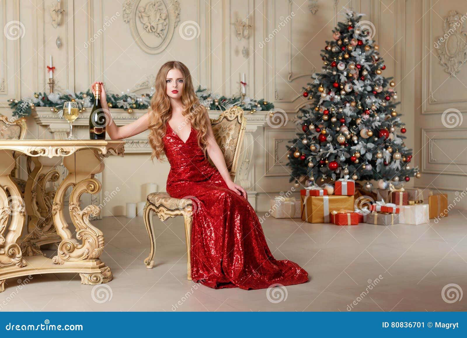 Blond kvinna i röd klänning med exponeringsglas av vitt vin eller champagne som placerar på en stol i lyxig inre jul min version