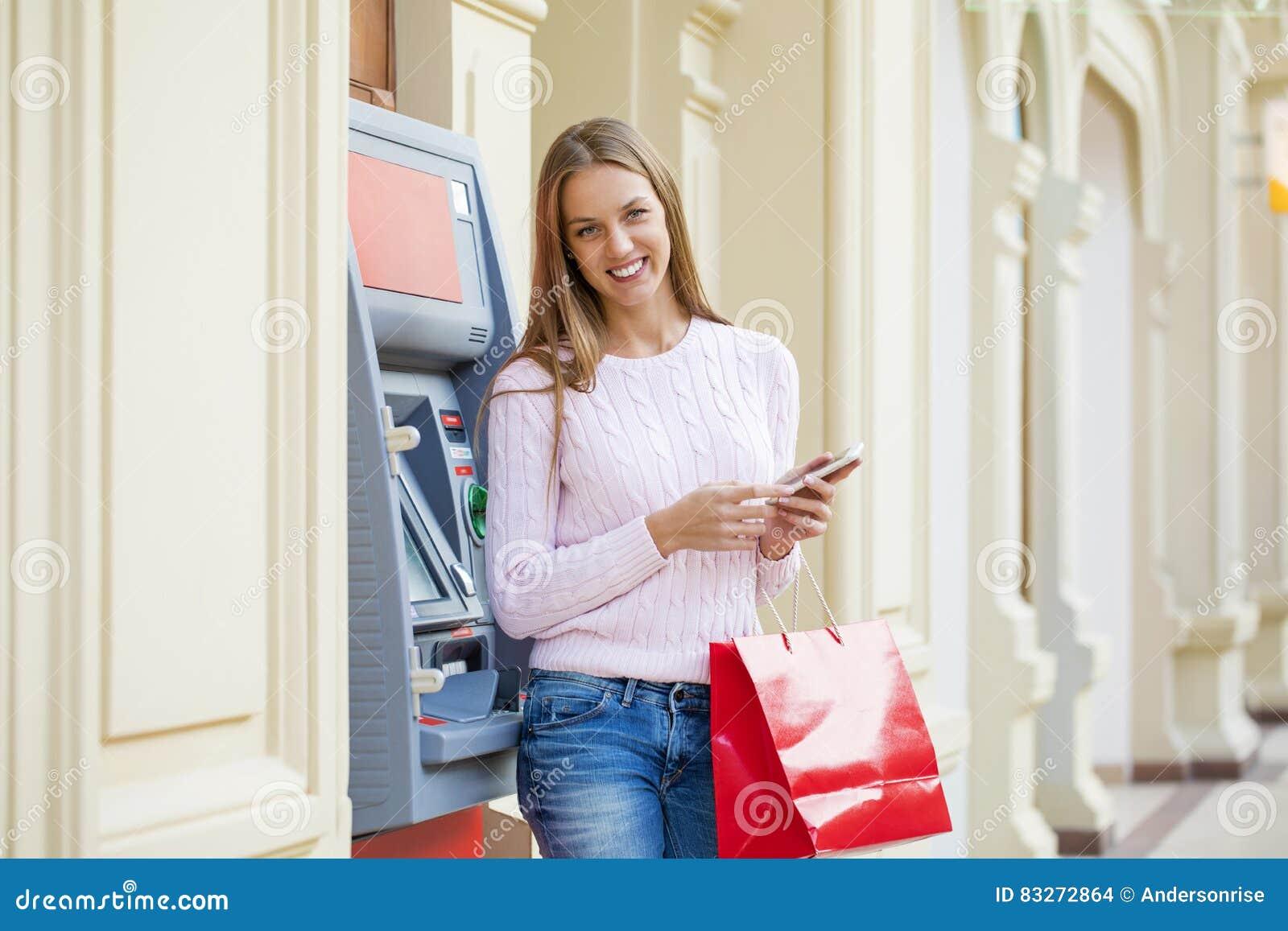 Blond kvinna på bakgrunden i köpcentret ATM