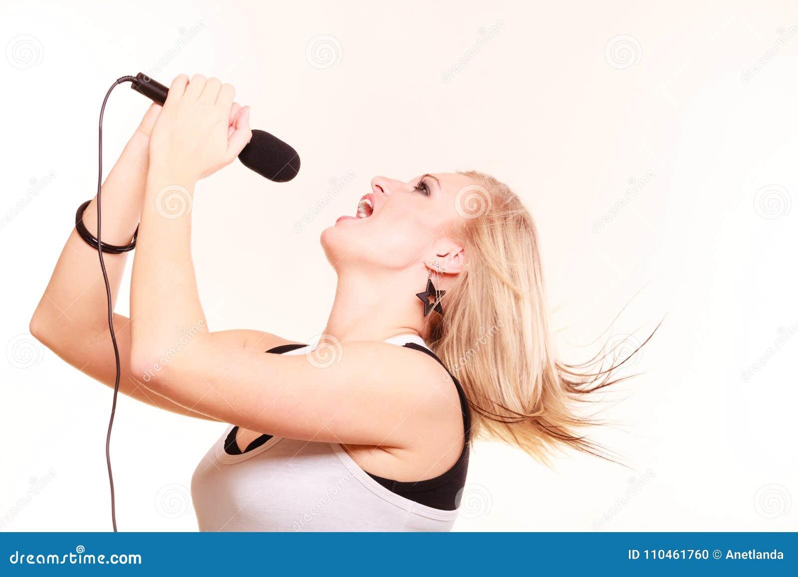 Blond kvinna som sjunger till mikrofonen, profilsikt