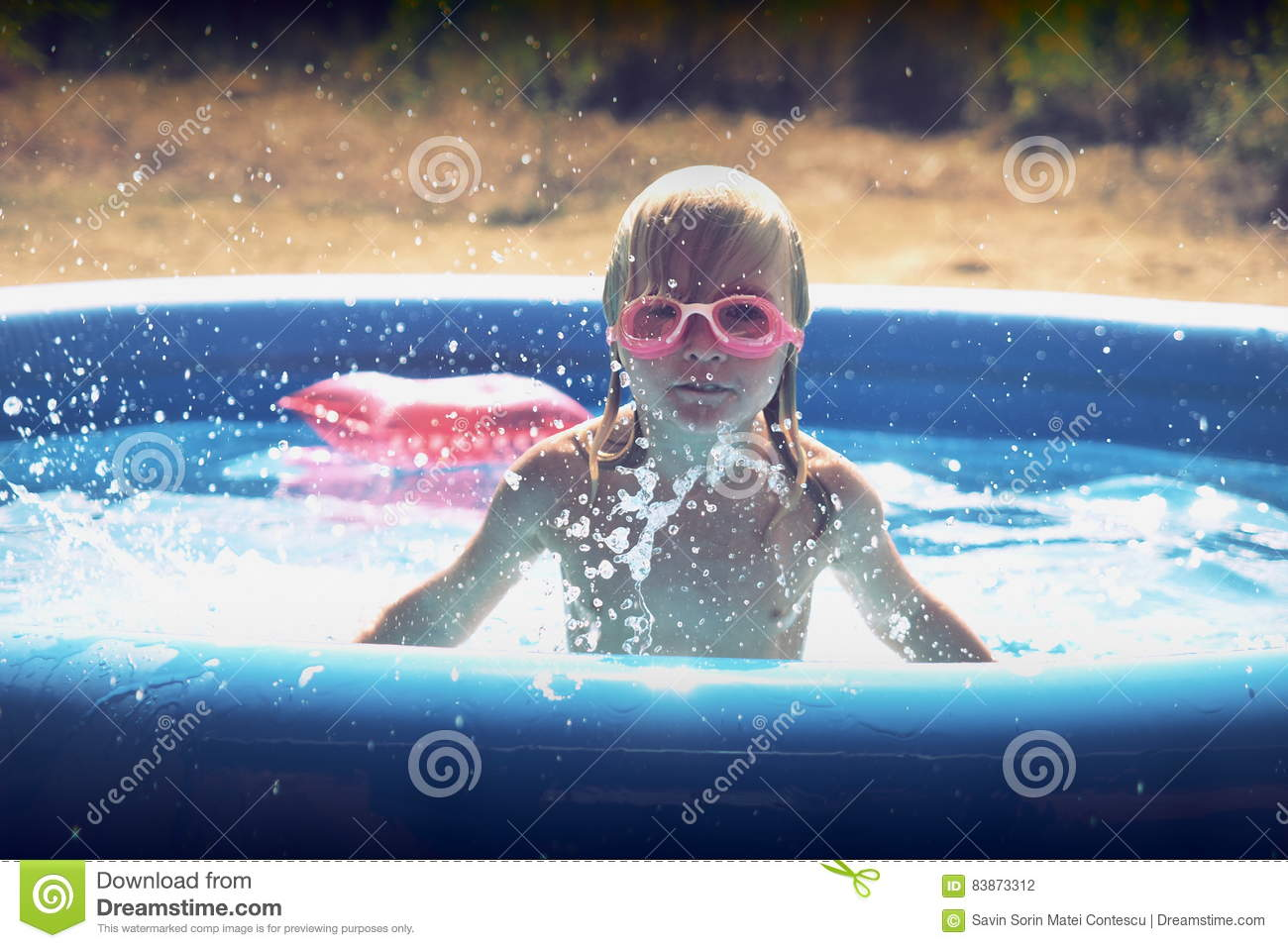 Blond little girl playing in the pool
