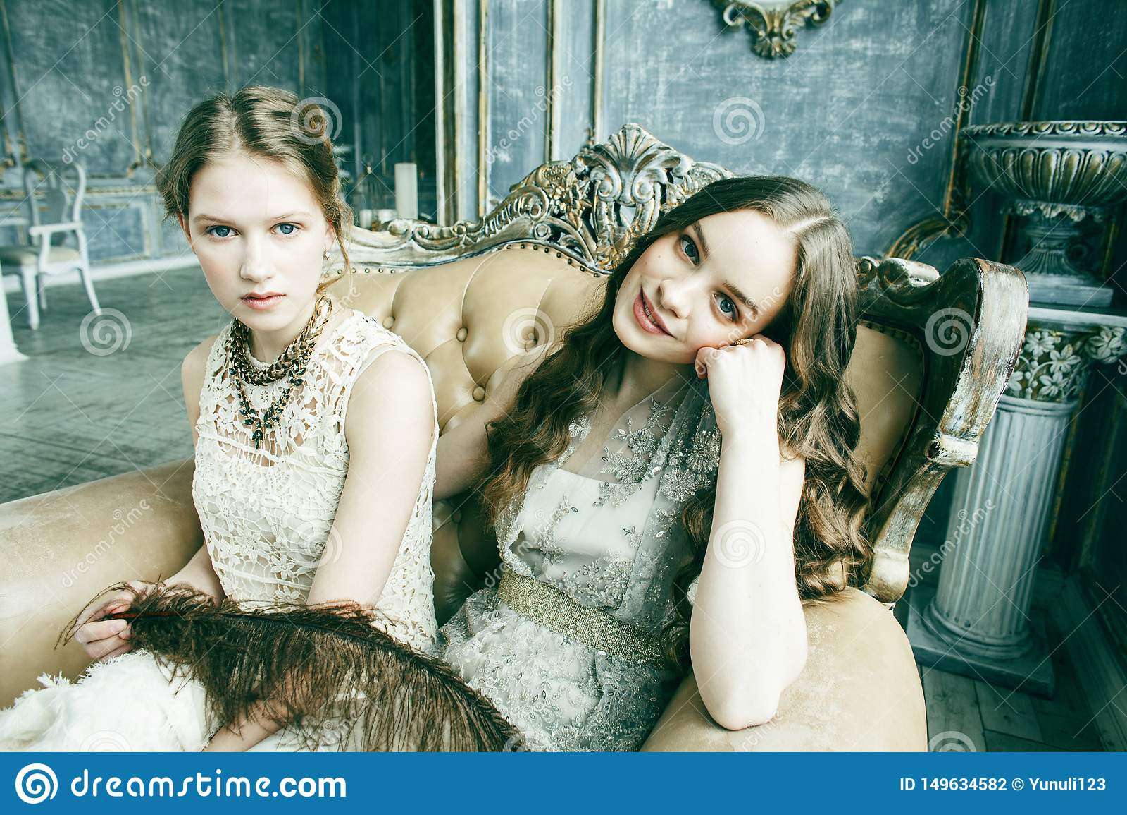 Blond lockig frisyrflicka f?r n?tt tvilling- syster tv? i lyxig husinre tillsammans, rikt ungdomarbegrepp