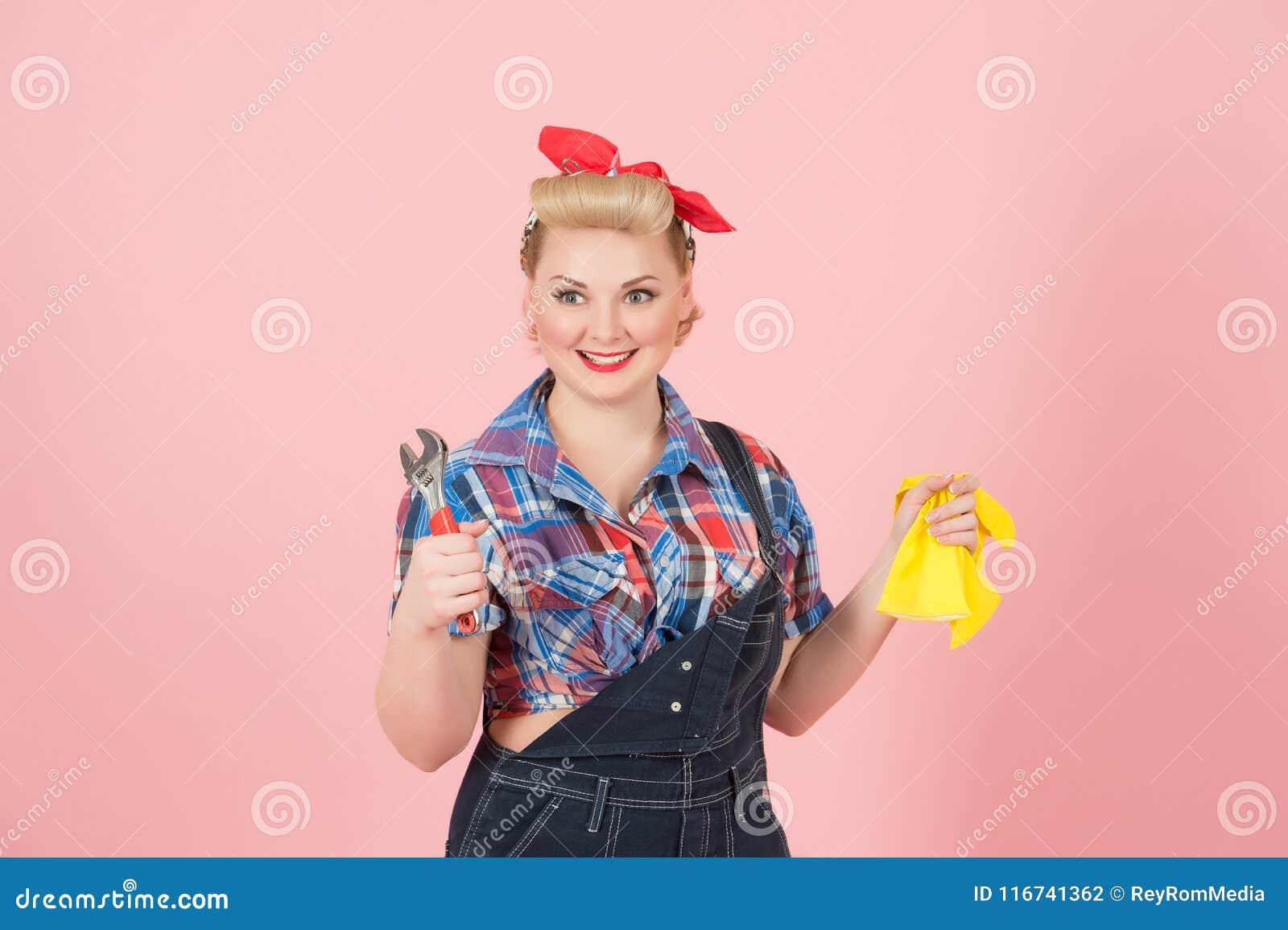 Blond lycklig le kvinnlig i handskar för latex för guling för utvikningsbildstilinnehav och skiftnyckel som isoleras på pastell-r