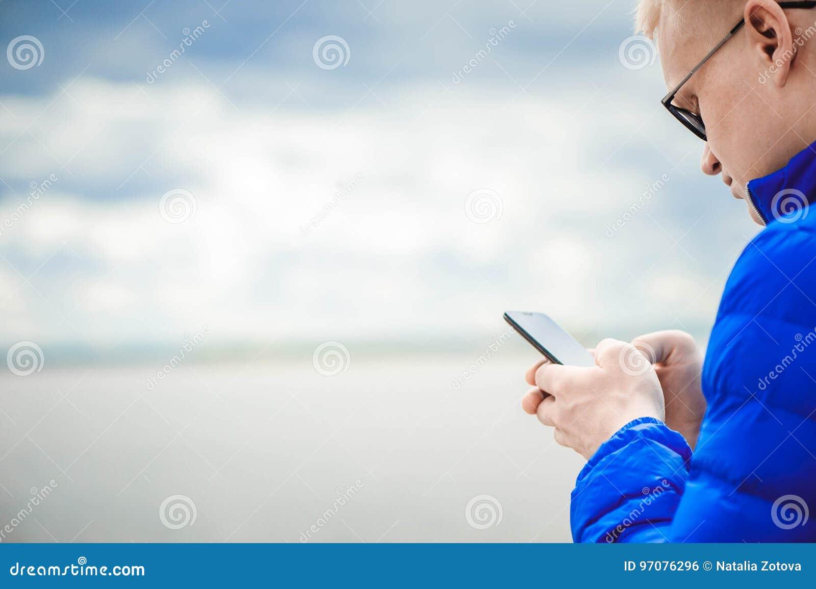 Blond man som använder mobiltelefonen på sjön