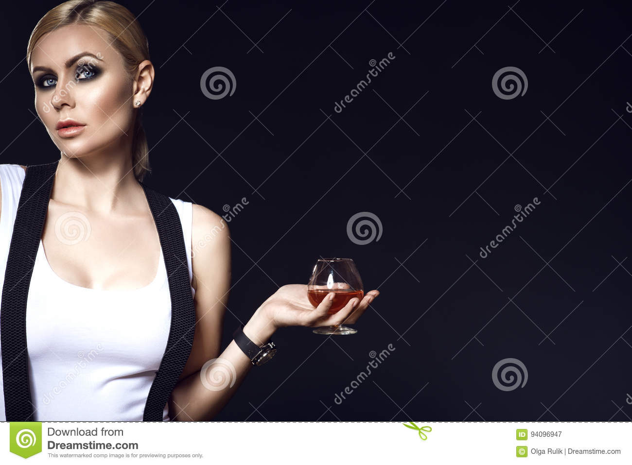 2f4f666d805a57 Portrait of chic blond model with pulled back hair and smoky eye make-up  wearing white top with suspenders over her shoulders and holding a glass of  brandy.