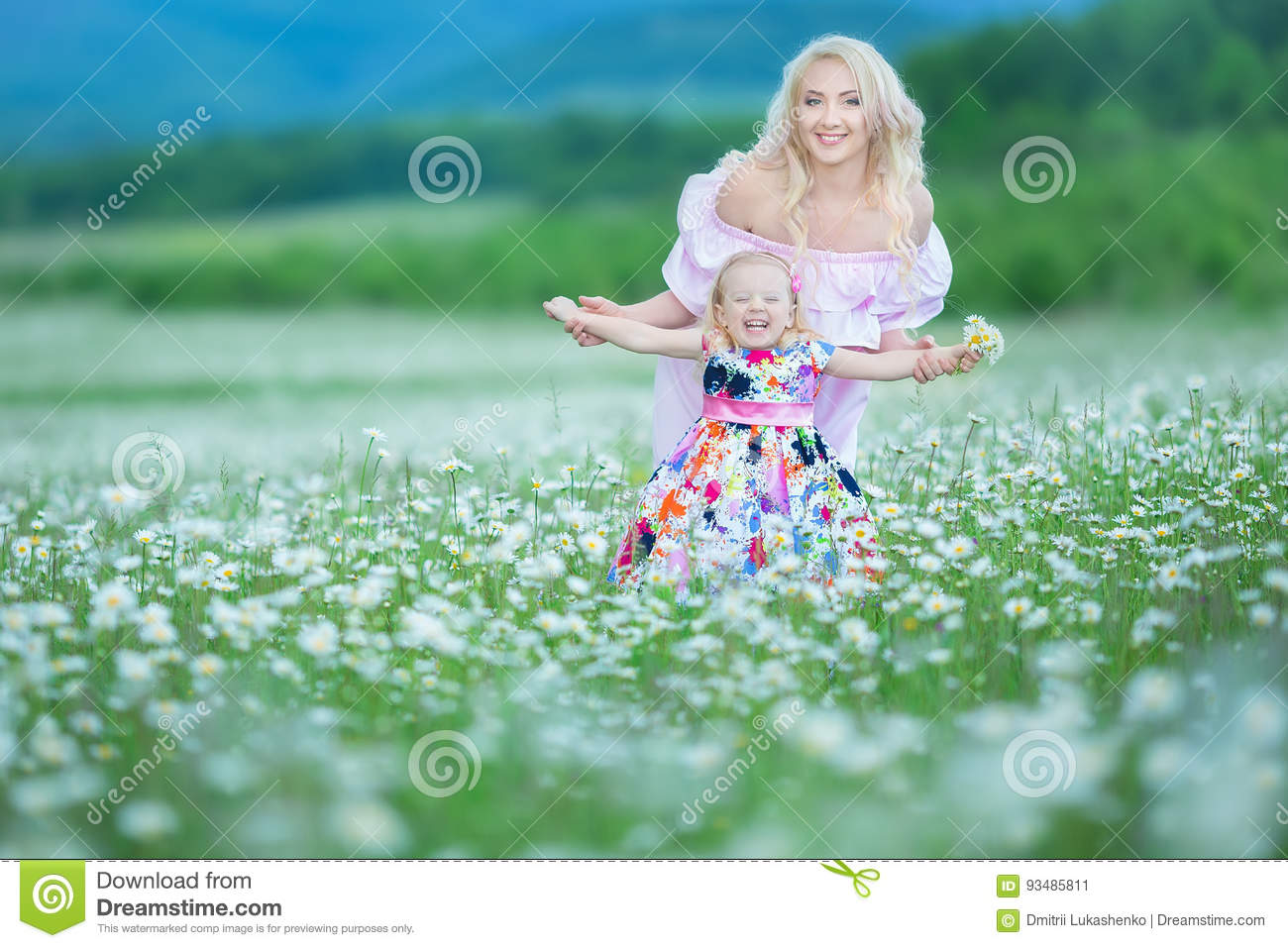 Blond mother with cute little daughter wearing white colourful pink dresses in chamomile field, summer time Enjoying spending time