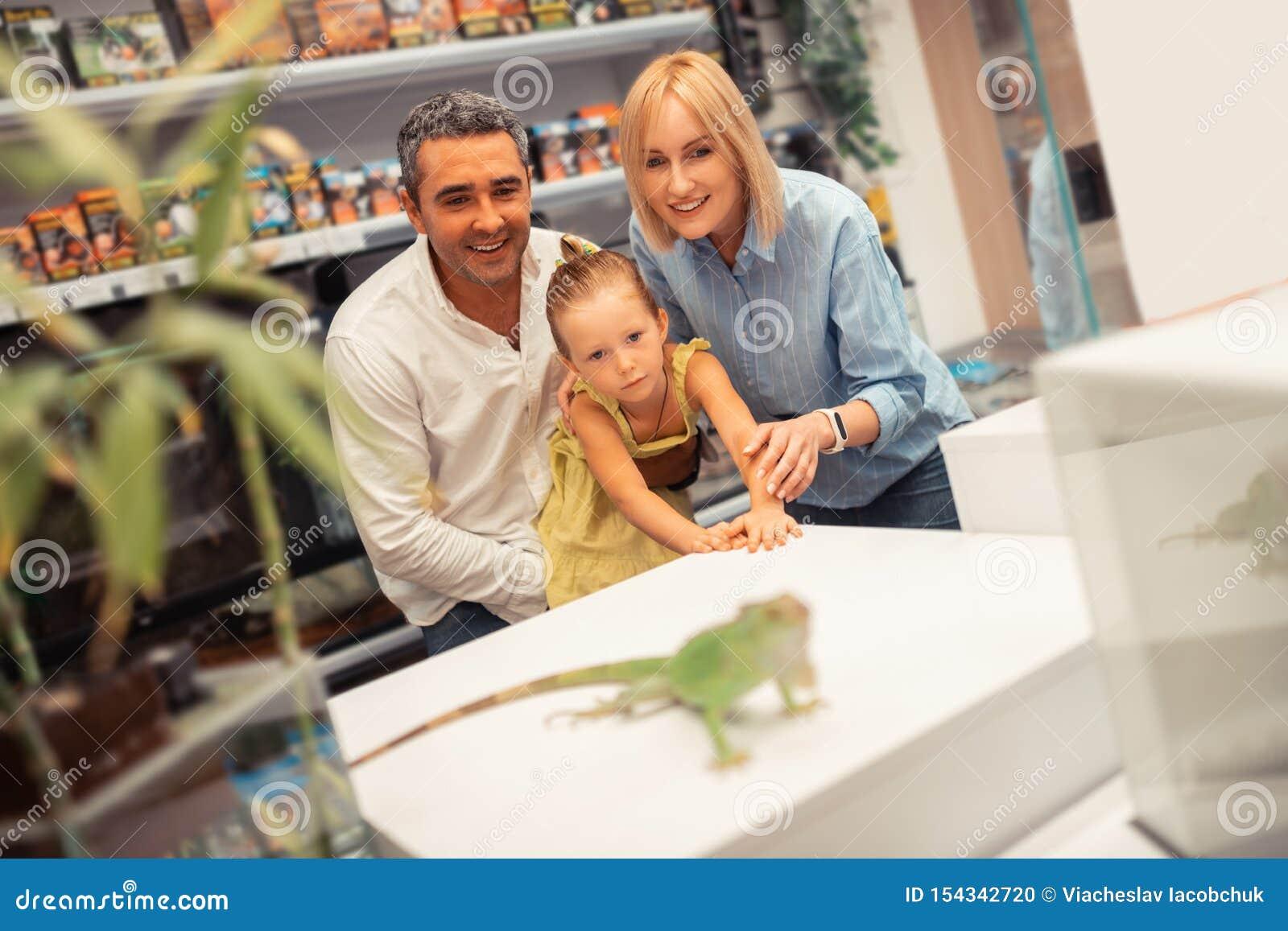 Blond spännande dotterkänsla, medan se leguanen med föräldrar