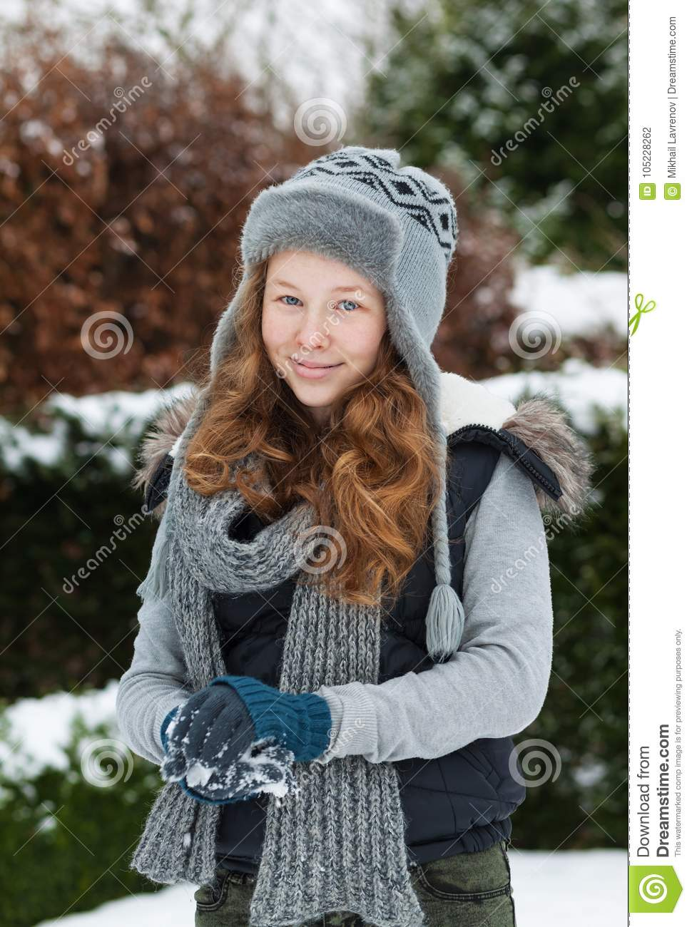 Blond teenager girl making a snowball in snowy park