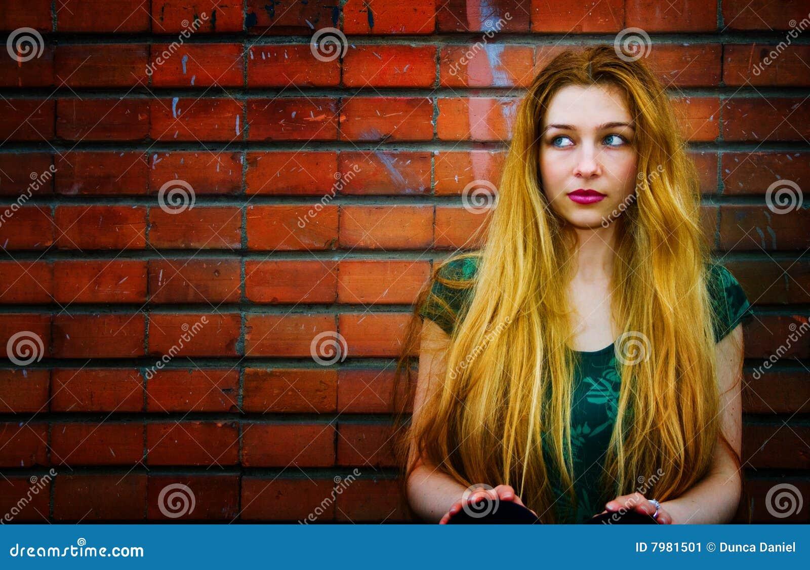 Blond tegelstenväggkvinna