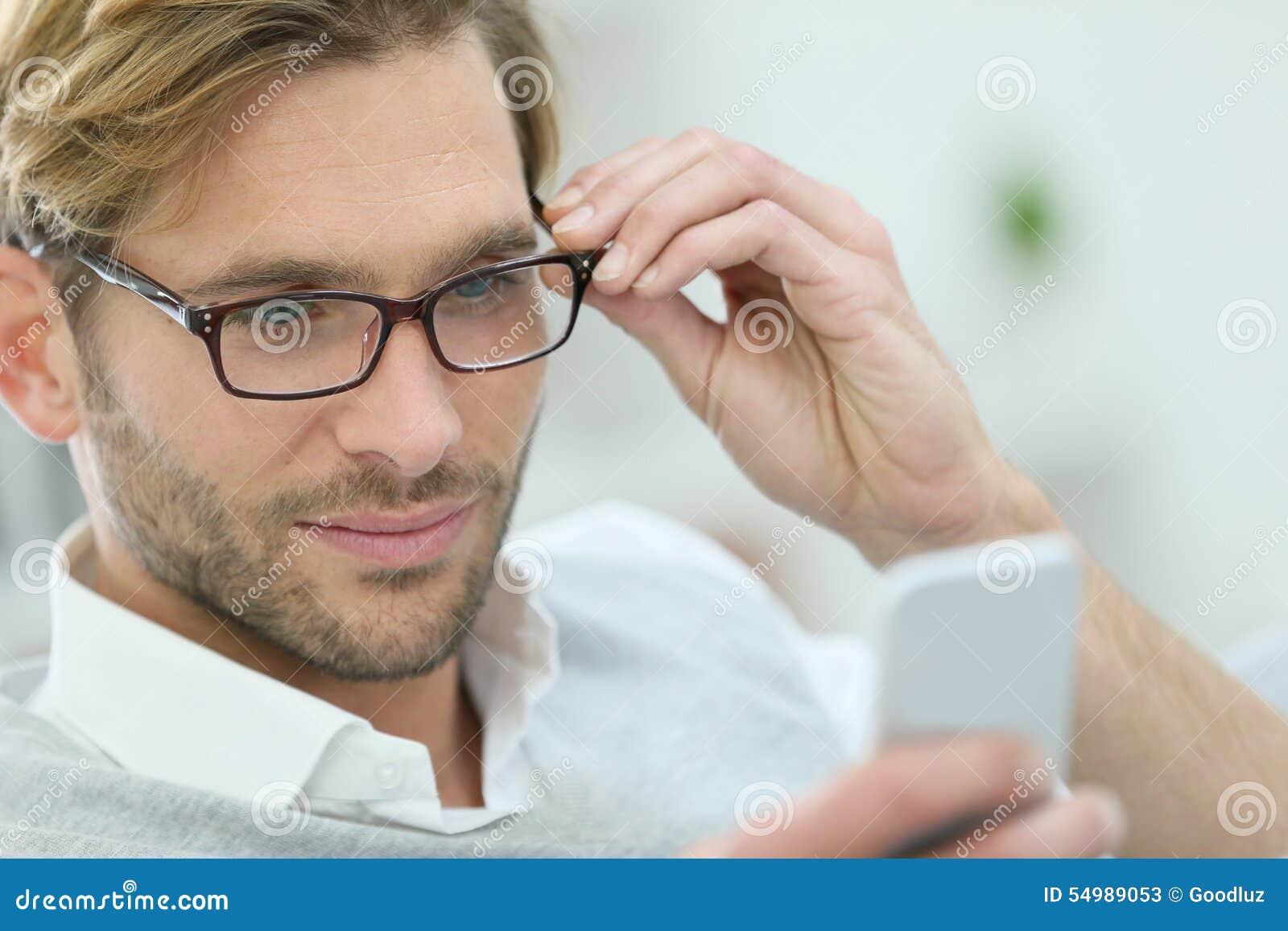 Blond ung man med glasögon genom att använda smartphonen