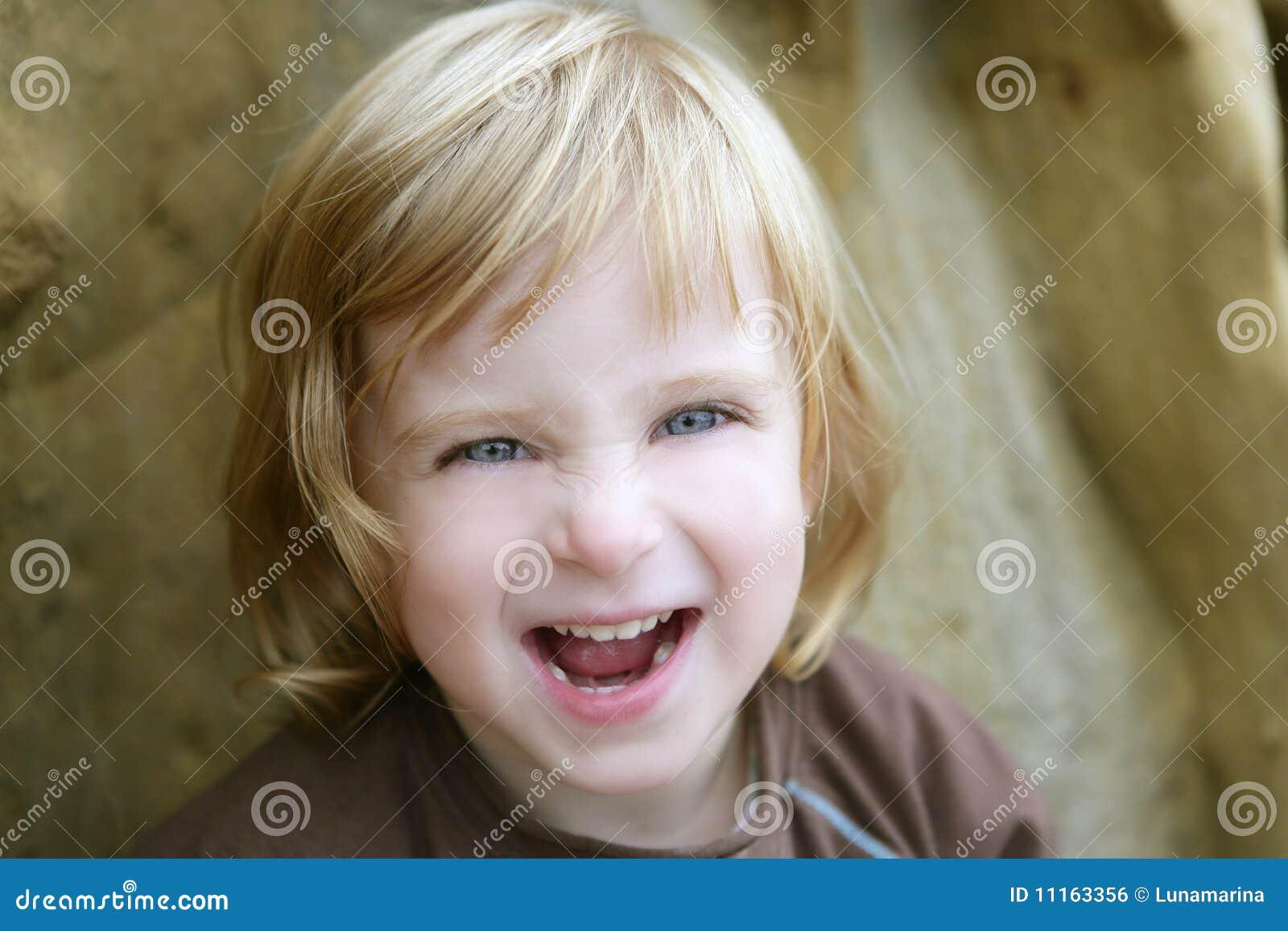 Blond weinig peutermeisje met grappig gebaar