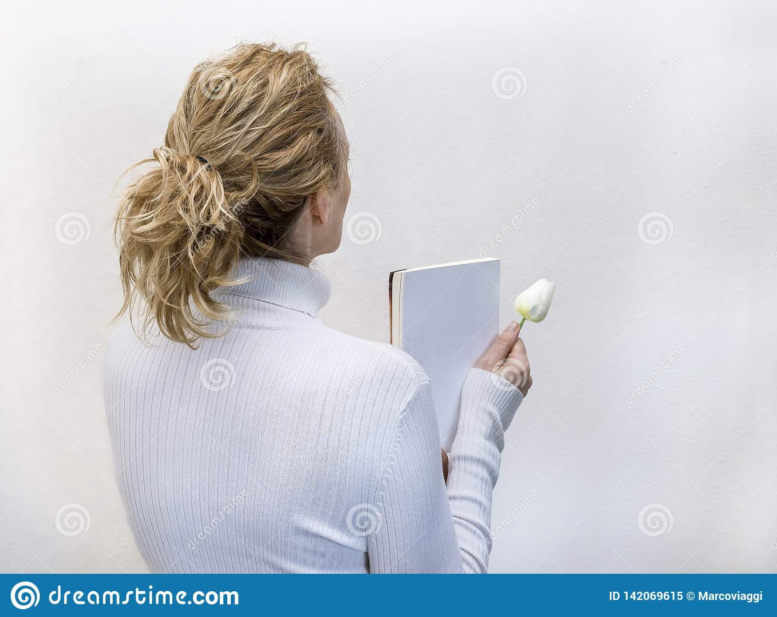 Blond woman dressed in white holding a book and a white flower against a completely white background