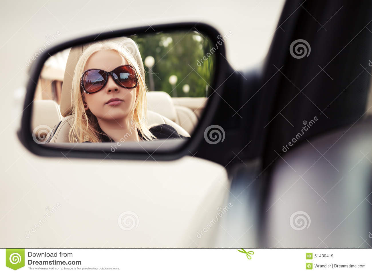 Blond woman looking in the car rear view mirror stock for Looking mirror