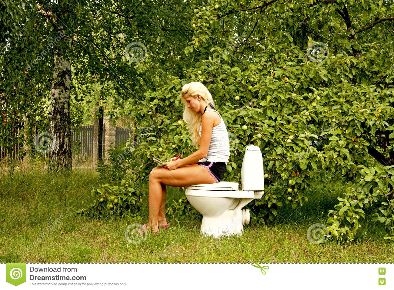 Blond woman sitting on a toilet bowl and reading a book