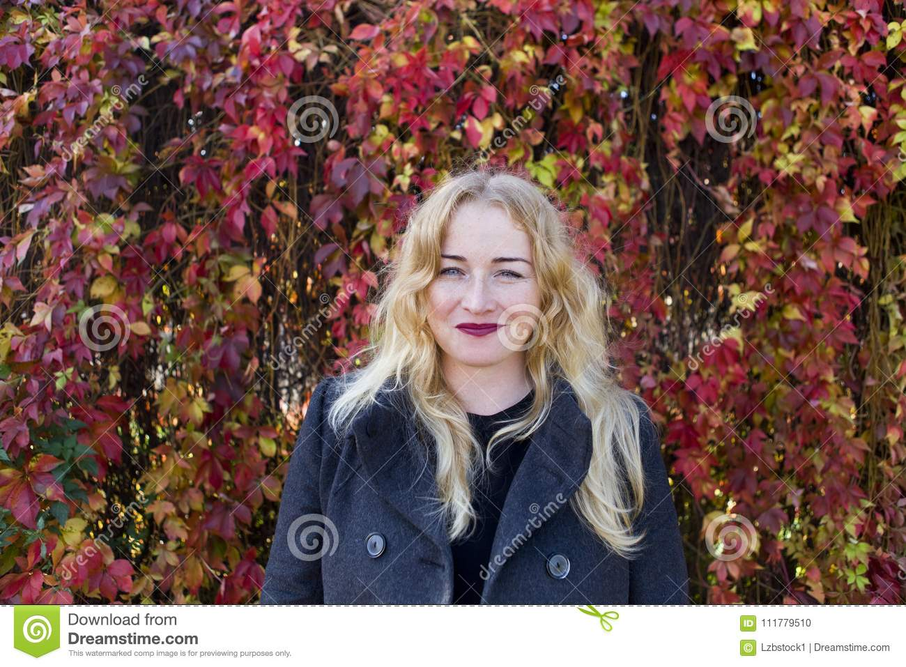 Smiling blond woman near colorful leaves