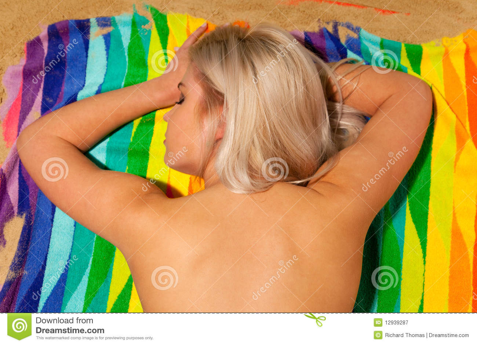 Blond woman sunbathing topless