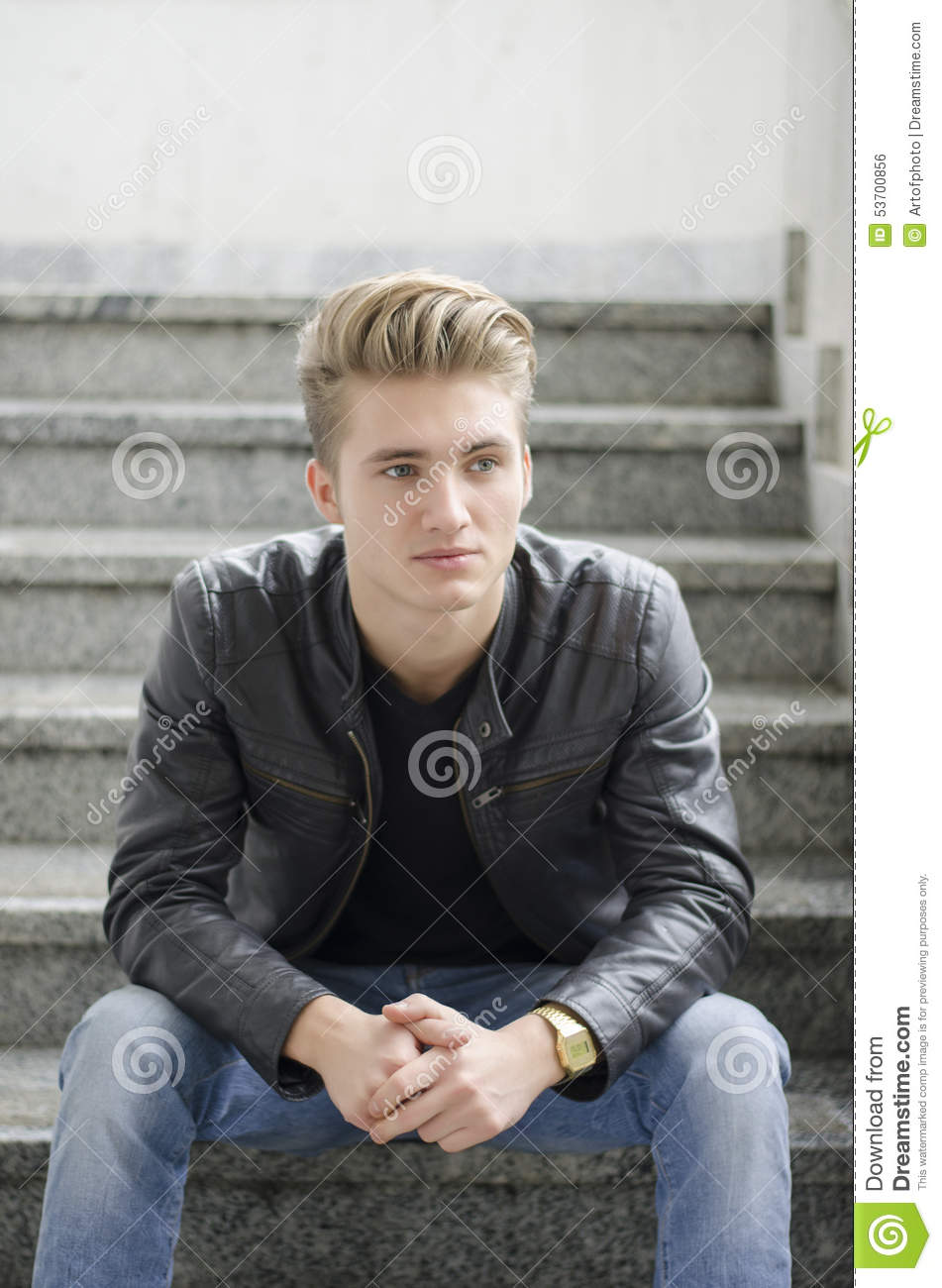 Blond Young Man Sitting On Stairs Outside Stock Photo